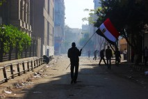 A protester with the national flag walks towards security forces in Cairo February 2012