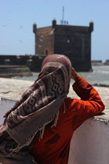 Maroccan woman gazing at fort in Essaouira
